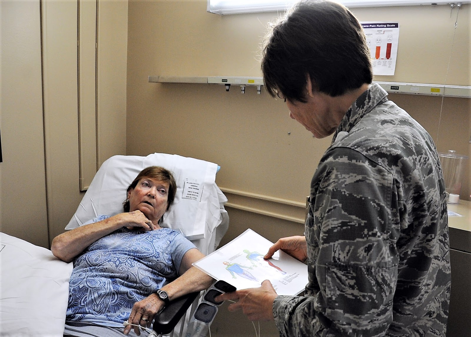 A patient talks to a military nurse from a hospital bed