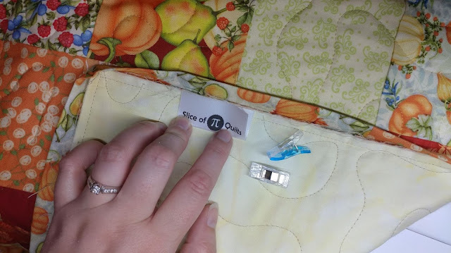Adding a satin label into the binding of a quilt