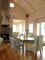 Cottage dining room design ideas with long wooden dining table and gray dining chairs on wooden floor also the candle chandelier and fireplace give some comfy to the dining area.