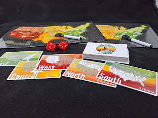 Two fold-out game boards with a map of the continental USA with dry-erase markers, laid out behind a stack of cards and two large ten-sided dice. Five cards have been turned over: one shows Nevada with the southern half of the country highlighted, another shows Montana in the highlighted North half, one shows New Mexico in the highlighted West region, one shows Kansas in the Central section, and the last one shows Mississippi in the highlighted East region.