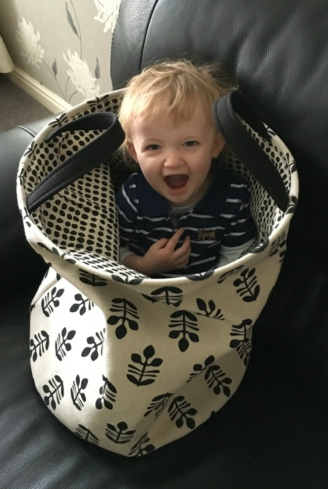 Happy toddler sat in washing basket with mouth wide open as if shouting