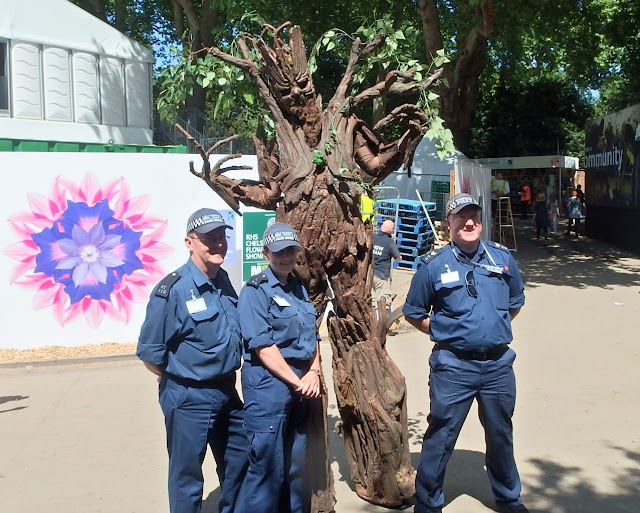 A surprise wandering tree pauses to pose with security officers at Chelsea Flower Show