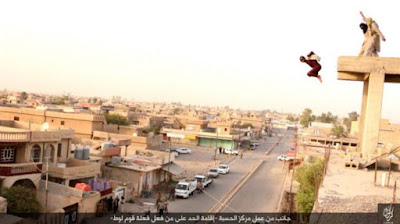 Image released by ISIS showing two of its militants throwing a man off a roof in southern Kirkuk for being gay.