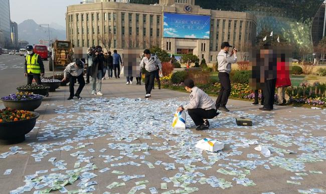 Policías coreanos recogiendo dinero del suelo en Seúl