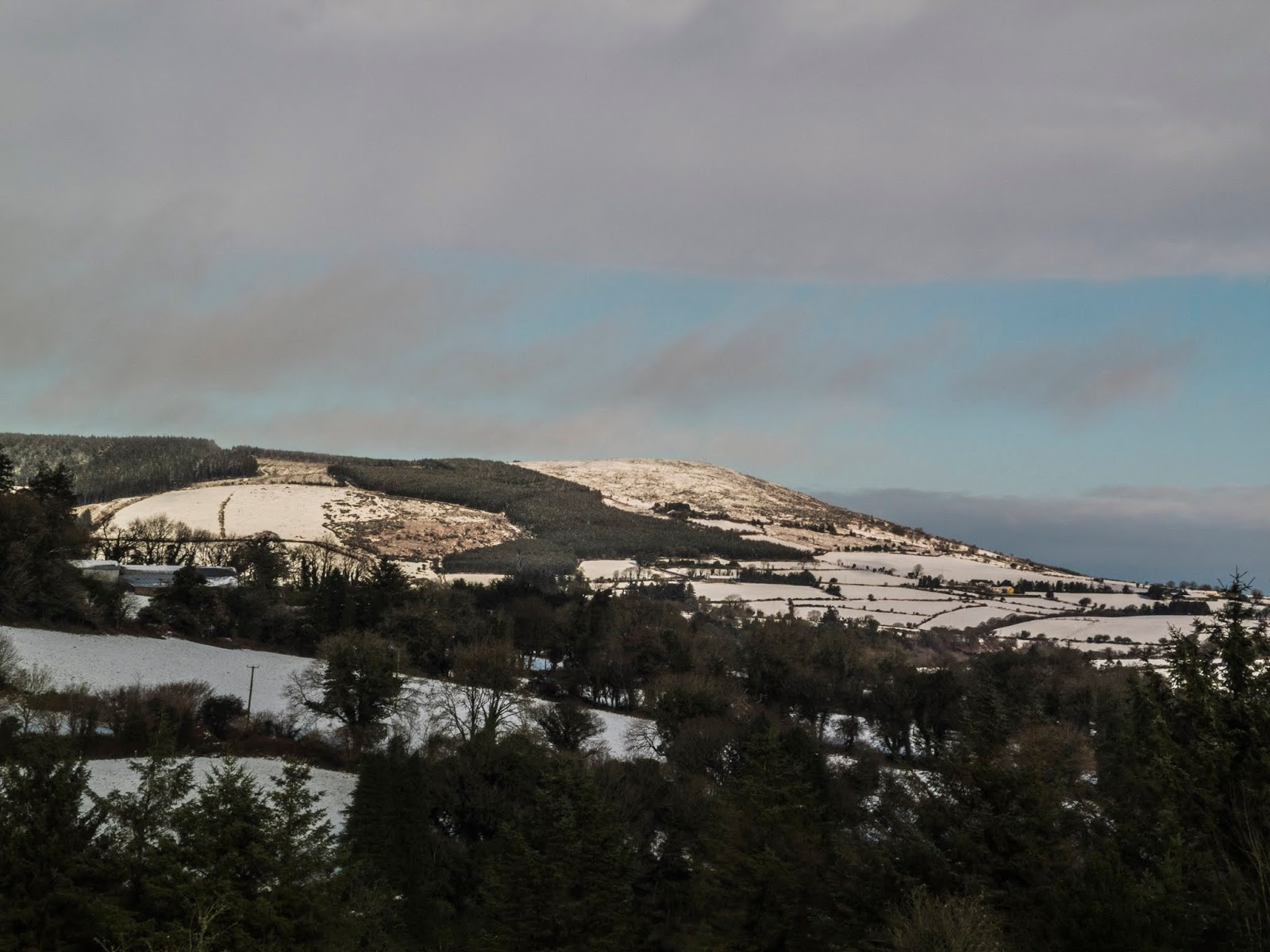 Sun shining on a snow covered mountain in North County Cork.