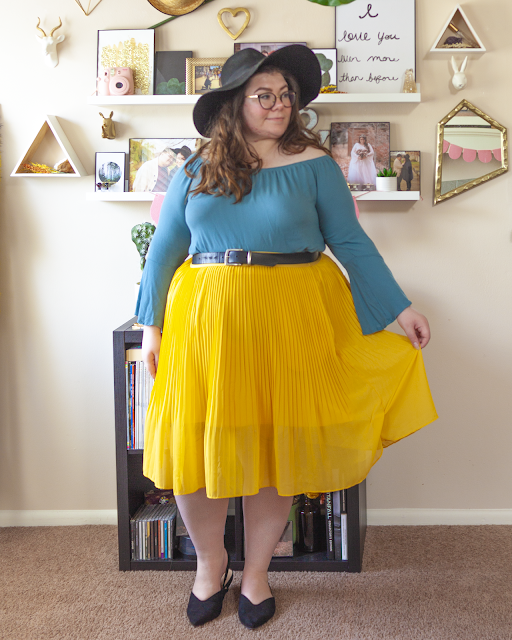 An outfit consisting of a black wide brim floppy hat, a blue off the shoulder blouse with bell sleeves tucked into a yellow pleated midi skirt and black pointed toe slingback heels.