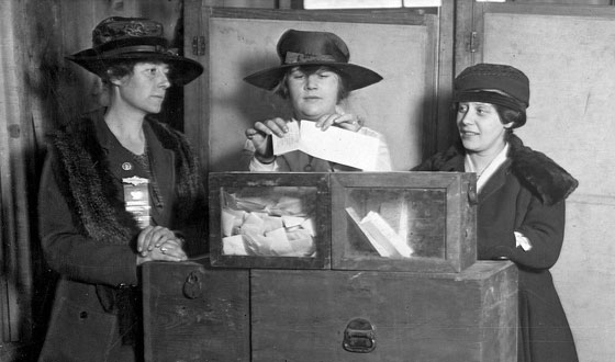 Description: black-and-white photo of three women in early 20th Century clothes, at a wooden ballot box. The woman in the center folds her ballot to place in the box.
