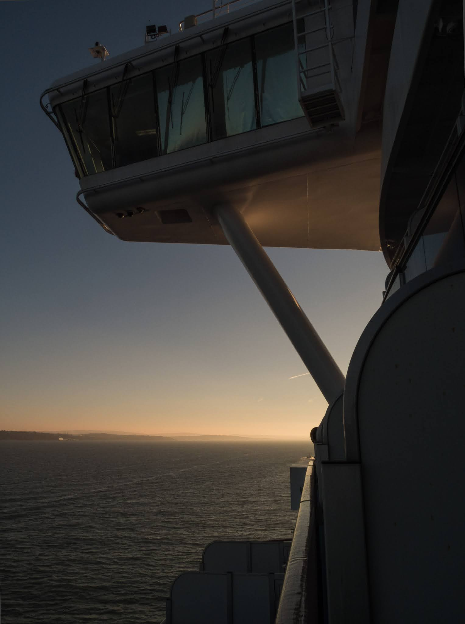 Setting sun reflecting of the port side of a cruise ship's bridge.