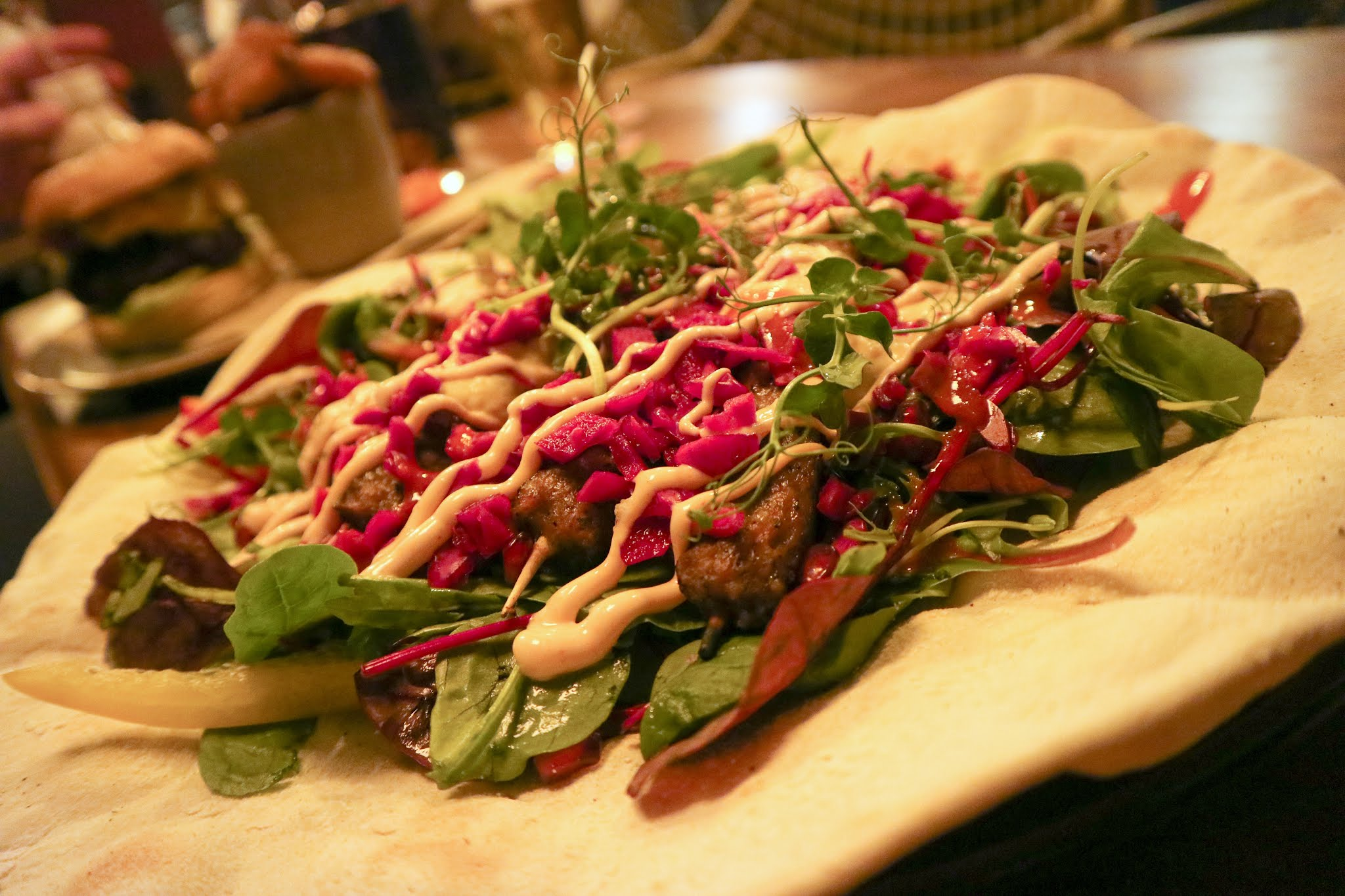 A large lamb kebab from The Ship's Cat food menu, with pomegranate seeds and salad