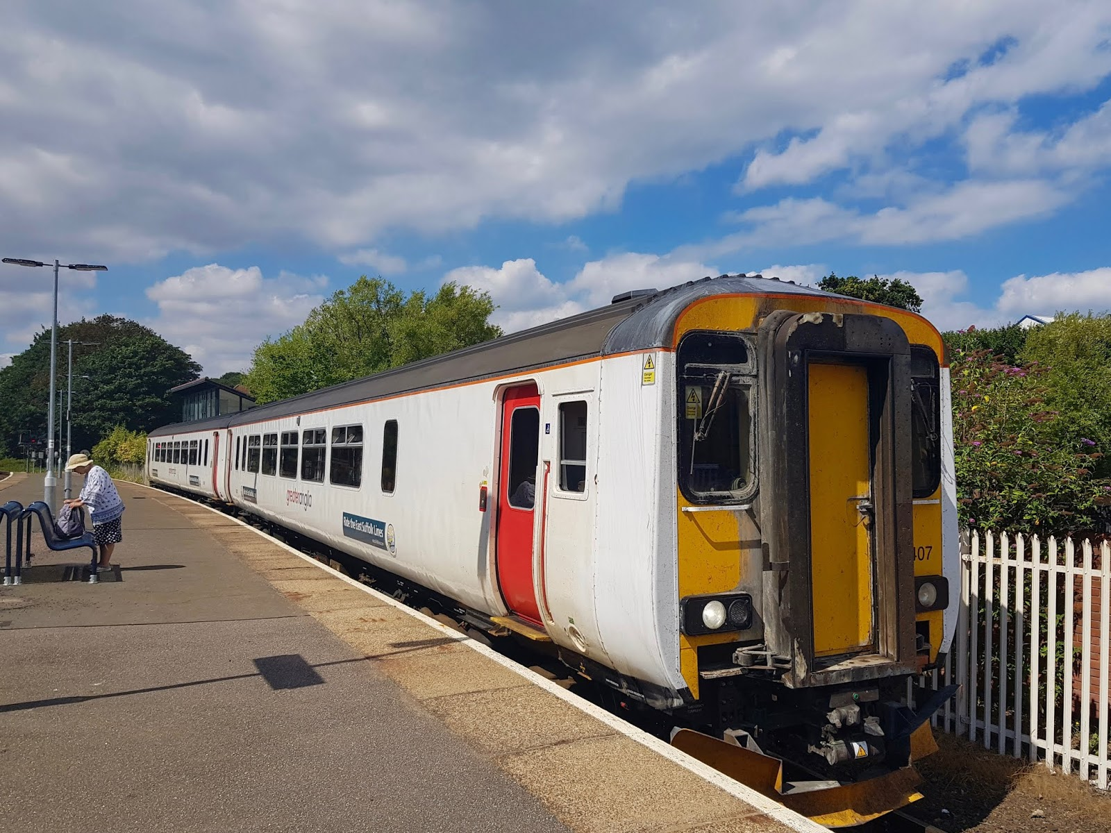 greater anglia train parked at station with passenger ready to board