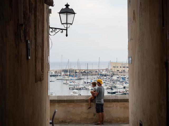 Padre e hijo de espaldas apoyados en la muralla con vistas al puerto de Otranto