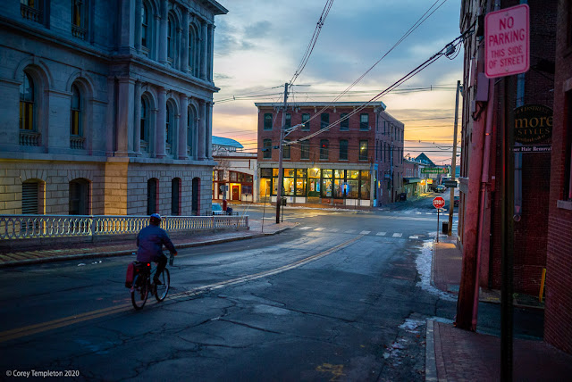 Portland, Maine USA December 2020 photo by Corey Templeton. A cyclist making their way down Pearl Street in the early morning.