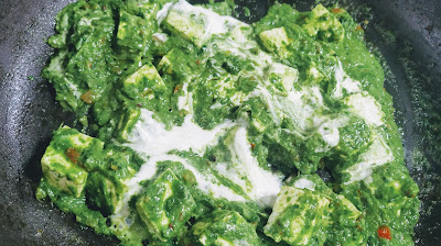Cooking palak paneer with adding cream for Palak Paneer recipe