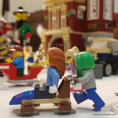 LEGO scene with child in hood pushing girl on sleigh with village behind.