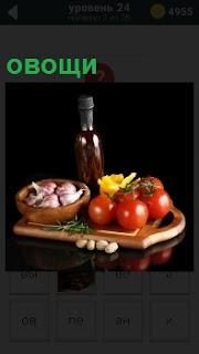 На подносе положены овощи. В миске лежит чеснок, рядом помидоры и стоит закрытая бутылка с темной жидкостью