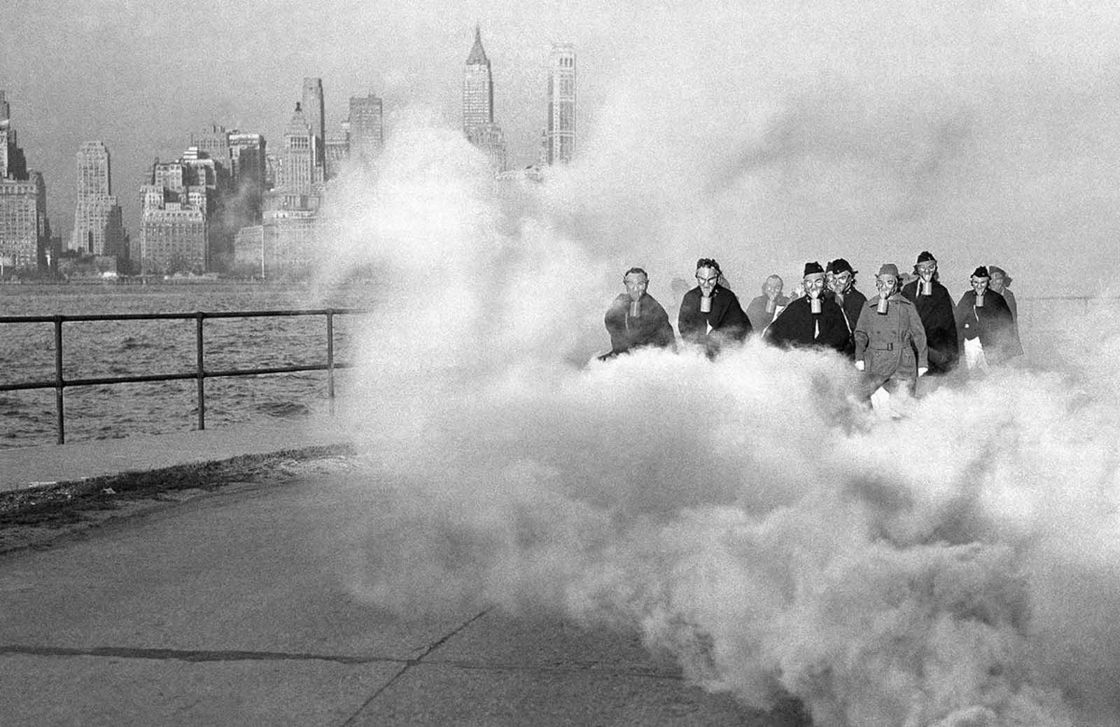 El 27 de noviembre de 1941, algunos de los rascacielos de Nueva York que se cernían sobre nubes de gas, algunas enfermeras del ejército de los EE. UU. En el puesto del hospital en Fort Jay, Governors Island, Nueva York, usan máscaras de gas mientras perforan las precauciones de defensa.