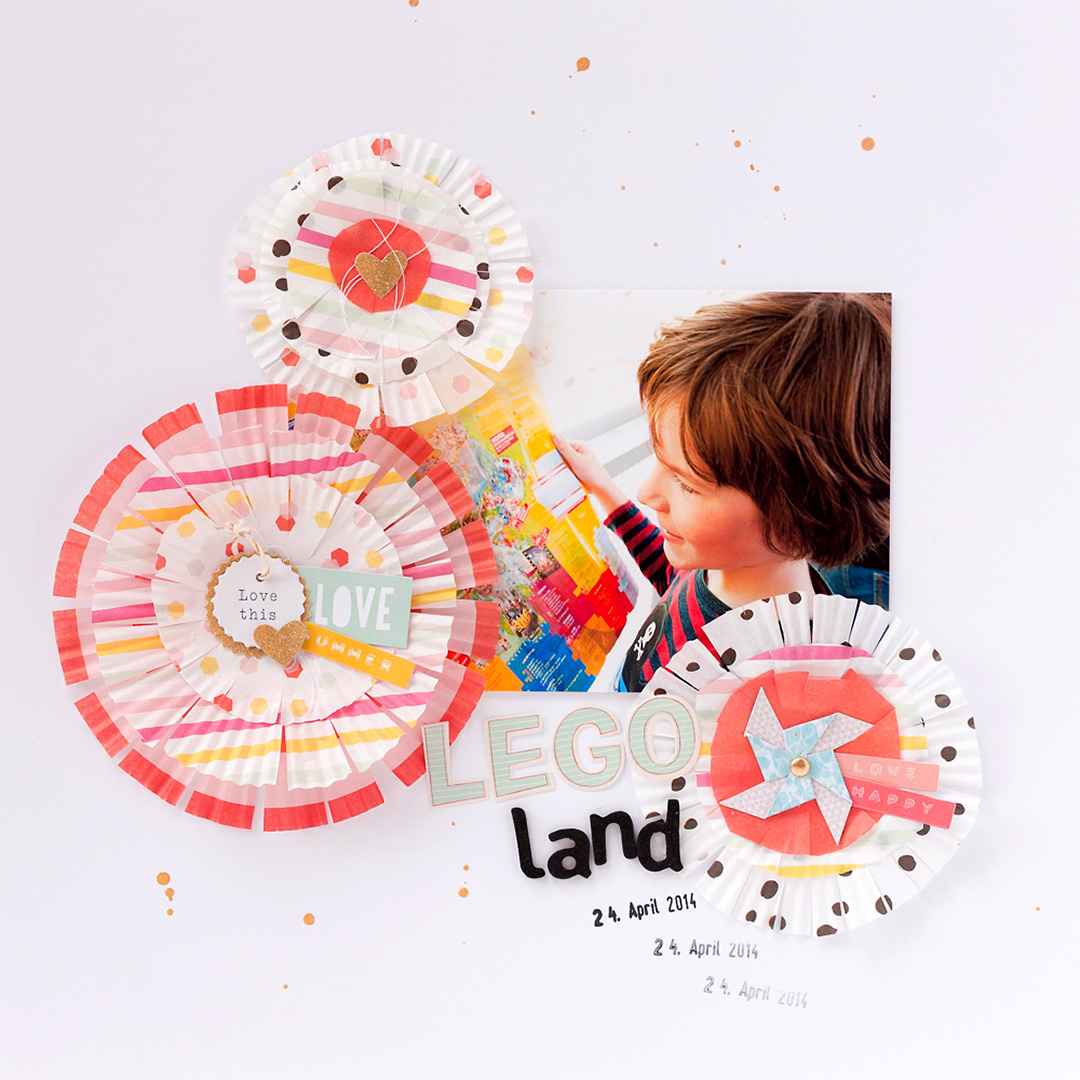 A scrapbook layout with handmade embellishments from cupcake liners. The title is Legoland 24th April 2014.