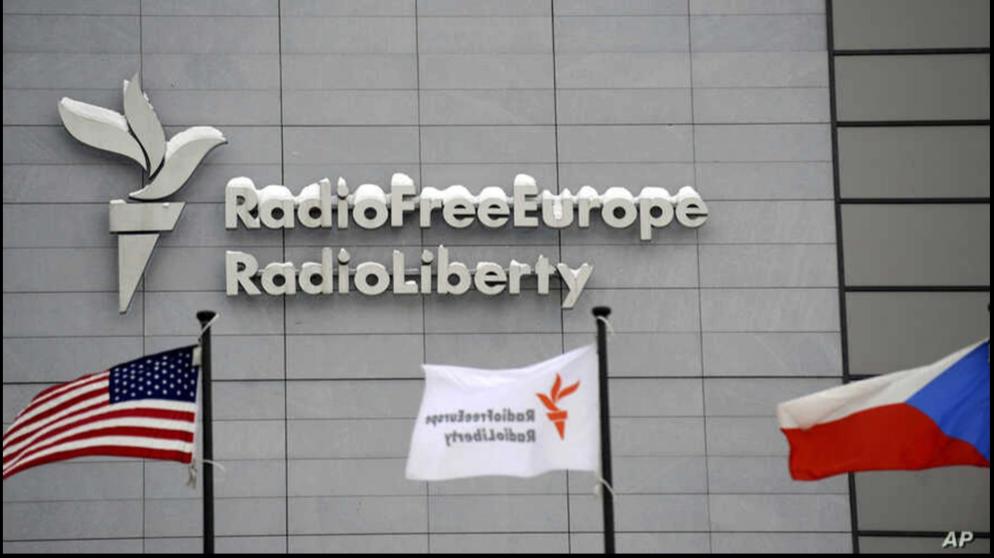 La sede de Radio Free Europe/Radio Liberty (RFE/RL) se ve con las banderas de los Estados Unidos, RFE/RL y la República Checa en primer plano, en Praga, 15 de enero de 2010 / AP
