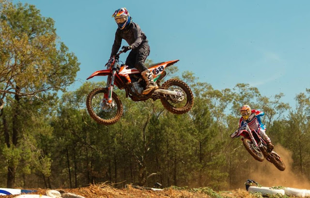 Two people dirt biking and jumping