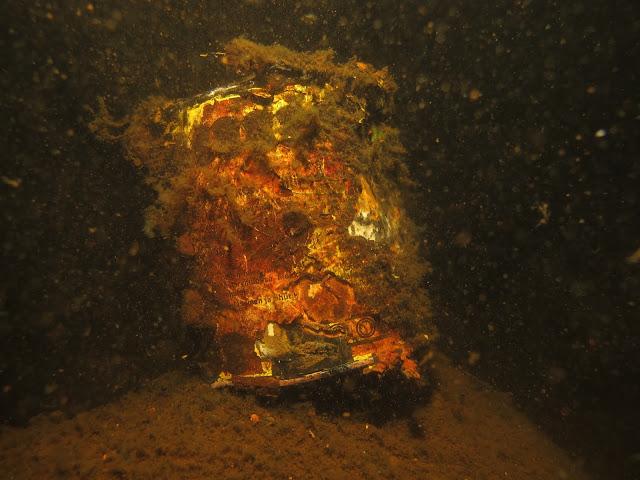 Ruostunut ja hapristunut metallitölkki meren pohjassa.