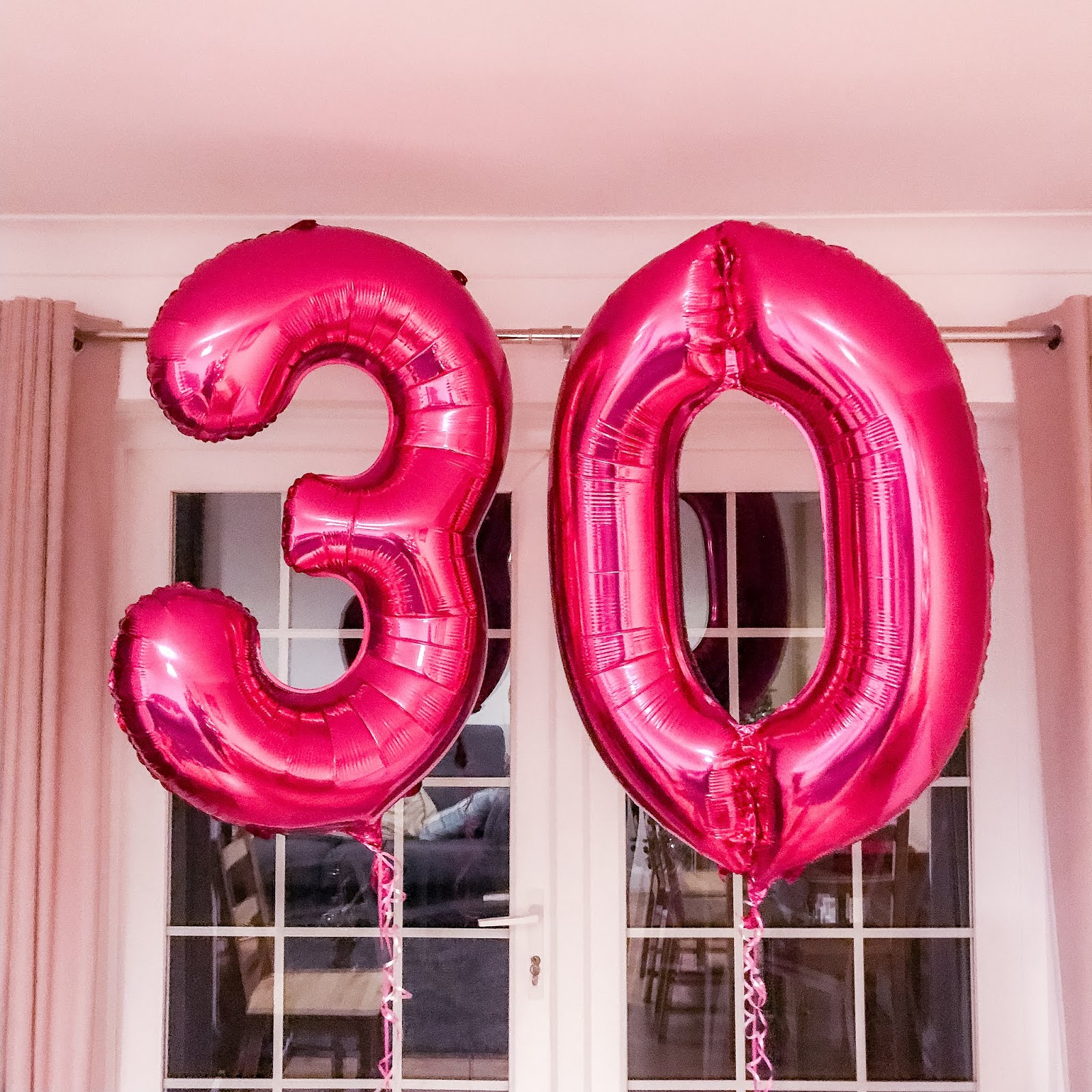 Two pink foil helium balloons writing out the number 30.