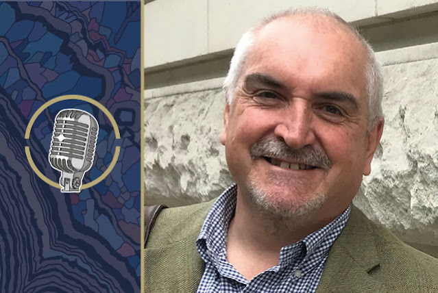 A picture of Andrew Bloodworth, smiling into the camera. The Rock the Mic logo is to the left of him, on the background of a graphic of the thin section of a rock.