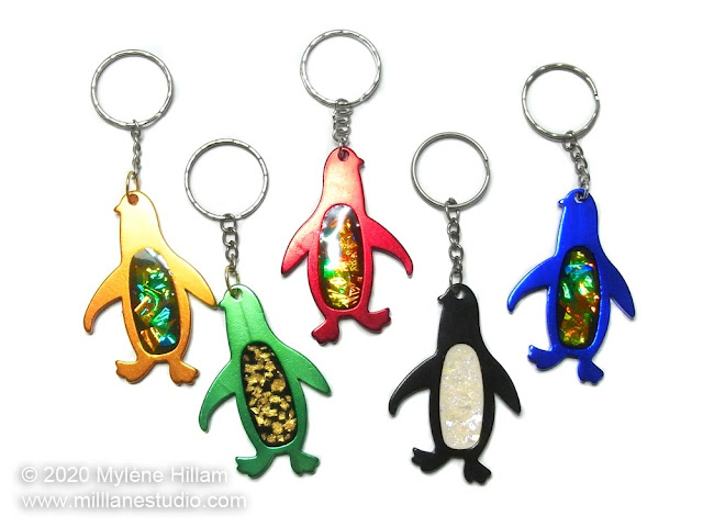 Five anodized penguin keychains filled with resin, iridescent mylar, gold leaf and glitter.