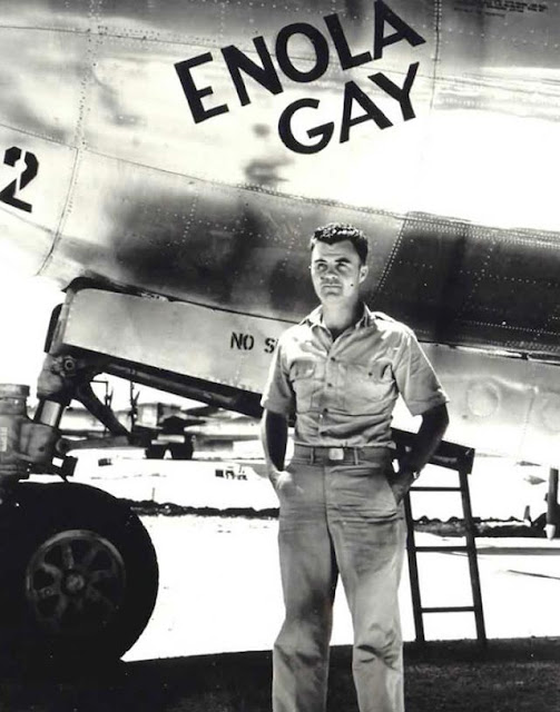 Paul Tibbets standing in front of his bomber named Enola Gay worldwartwo.filminspector.com