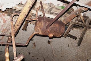 An der Decke hängt ein kleiner, alter und verrosteter Heizkessel, von dem aus viele ebenfalls verrostete Rohre abgehen.