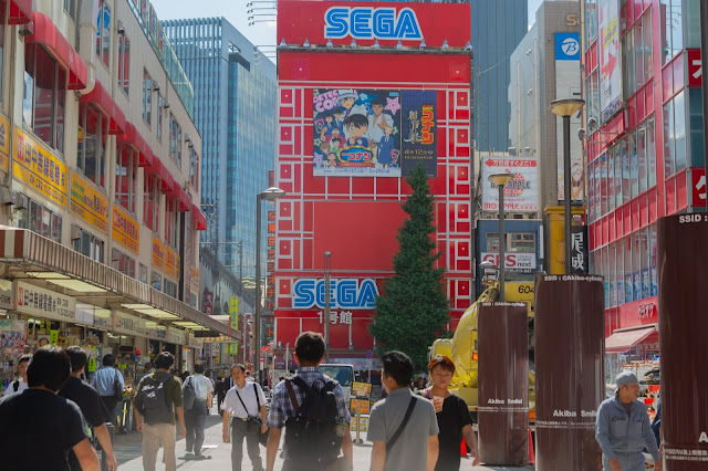Locals and tourists walking around Akihabara electric town in area near SEGA red building with Detective Conan billboard.
