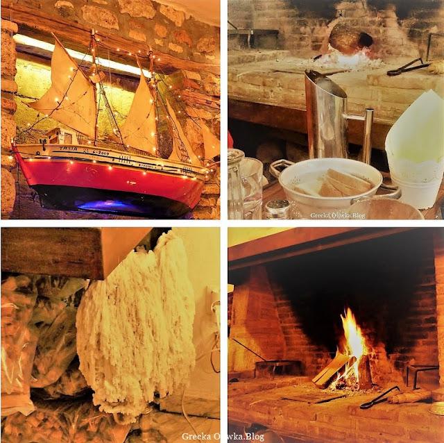 płomień w kominku w greckiej tawernie, czerwony dekoracyjny model statku, duża iliość białego ulanego wosku, kromki chleba w naczyniu z uchem