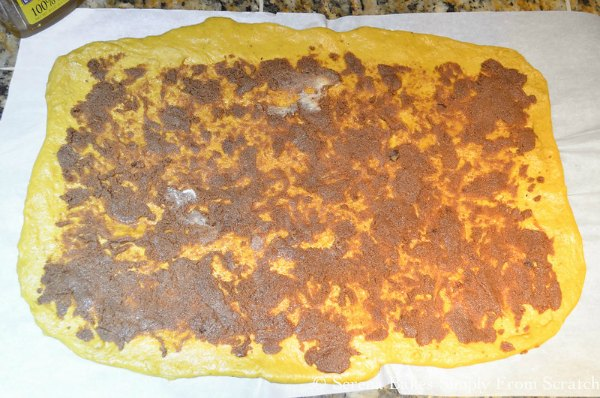 Spread sticky cinnamon filling over Pumpkin Cinnamon Roll Dough.