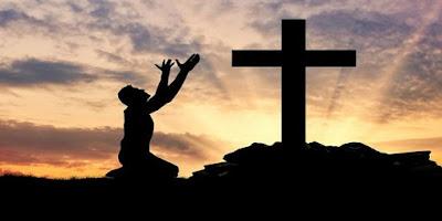 imagem de uma pessoa rezando diante da cruz de Cristo