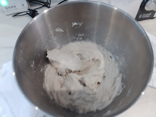 Metal mixing dough with a very sticky and wet bread dough in the bottom.