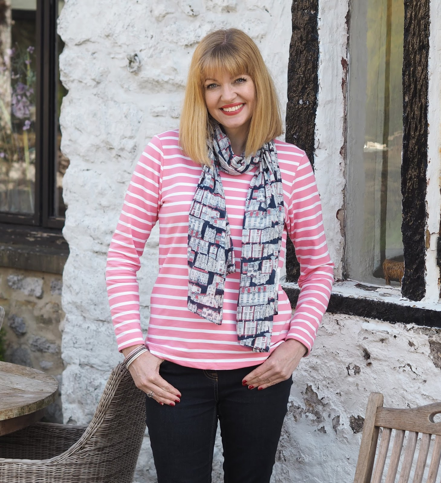 Half-length image of pink and white striped breton top by Tulchan with skinny jeans and silver Superga pumps