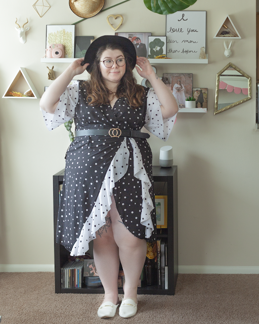 An outfit consisting of a wide brim black hat, a white on black polka dotted knee length wrap dress with black on white dotted flowy short sleeves and black on white dotted ruffle hem and white mules.