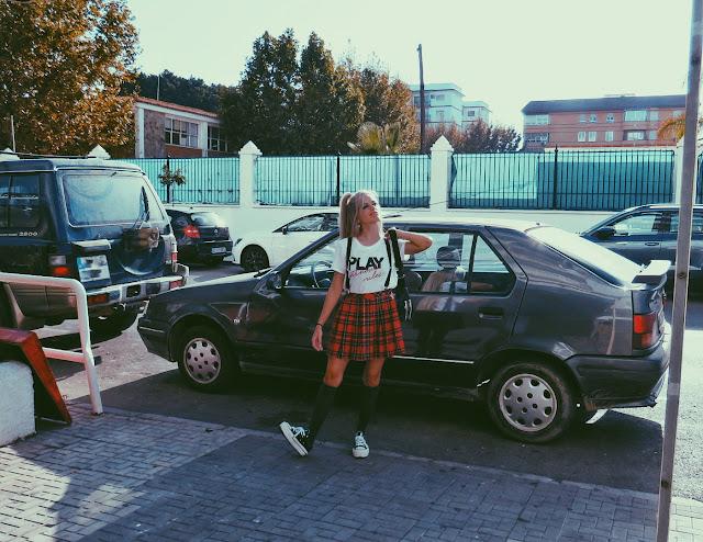 Alejandra Colomera vestida con camiseta blanca con mensaje, falda de tablas cuadros escoceses, tirantes, calcetas y zapatillas con Renault 19 de fondo
