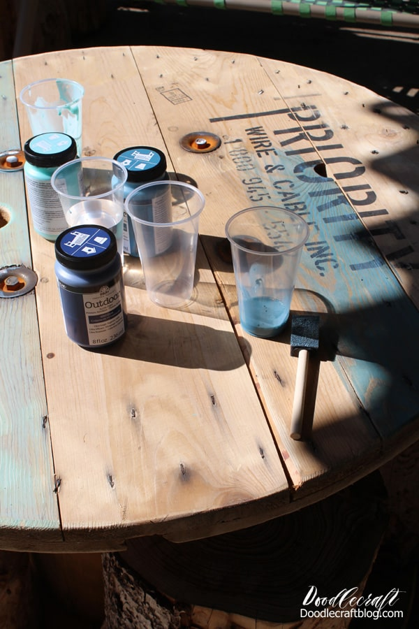 Upcycle a big wood spool into a patio table using nautical colored paints as a wash.