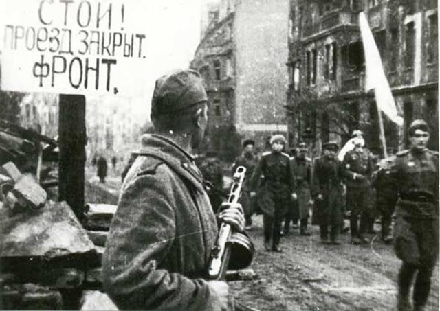 Żołnierz radziecki w Breslau w 1945 roku, w tle niemieccy żołnierze z białą flagą