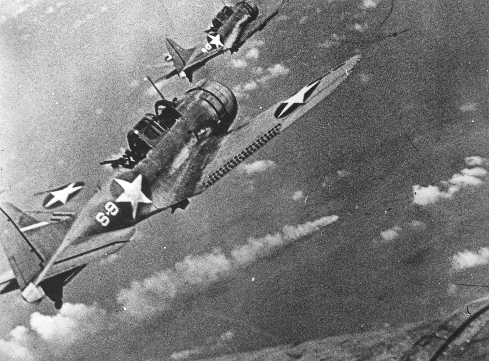 Navy fighters during the attack on the Japanese fleet off Midway, in June of 1942. At center a burning Japanese ship is visible.