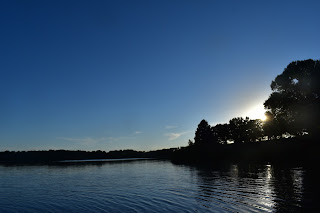 A calm lake at twilight, the far shore's oak trees are in shadow and the sun is about to slip behind them.