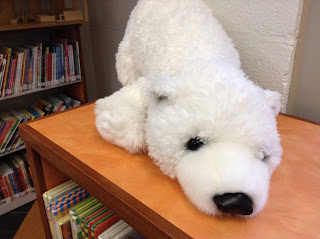 stuffed polar bear sitting on a shelf