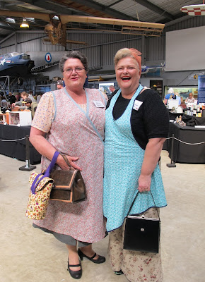 Two women dressed in 1940s outfits, standing in front of displays at a miniatures convention.