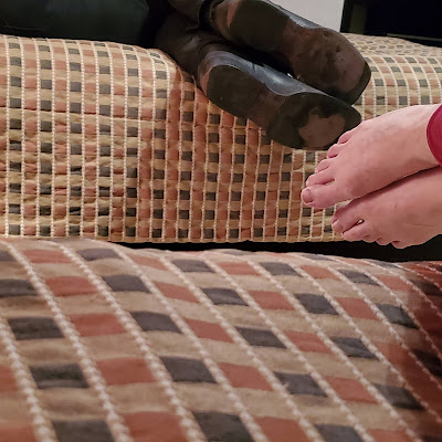 Two pairs of feet poking off the sides of beds. One pair is bare; you can see the tops of these feet. The pair other is wearing cowboy boots; you can see the worn soles of this pair.