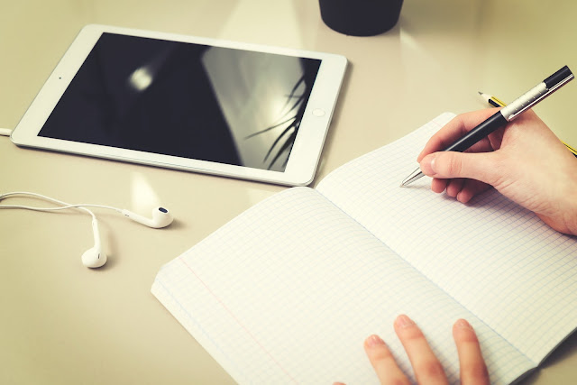 teenager writing in a notebook, ipad and earphones on desk