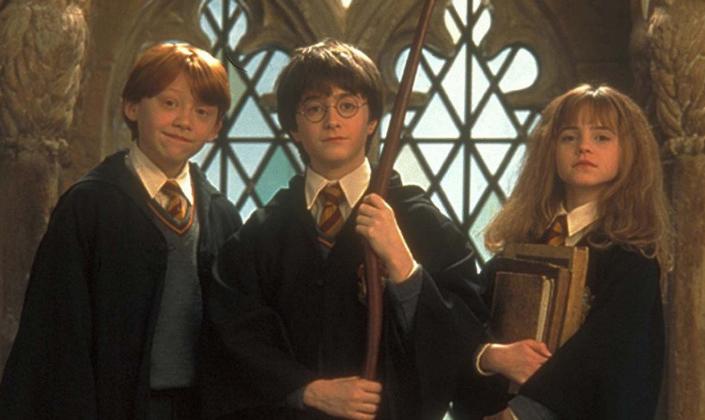Imagem de capa: foto promocional do trio protagonista de Harry Potter e a Pedra Filosofal, Rony Weasley, um garoto ruivo, Harry Potter, um garoto de cabelos pretos e óculos redondos no centro, Hermione Granger, uma garota de cabelos longos e desarrumados, segurando uma braçada de livros, em uniformes antiquados de escola com gravatas e longos casacos pretos com uma janela de castelo antigo ao fundo.