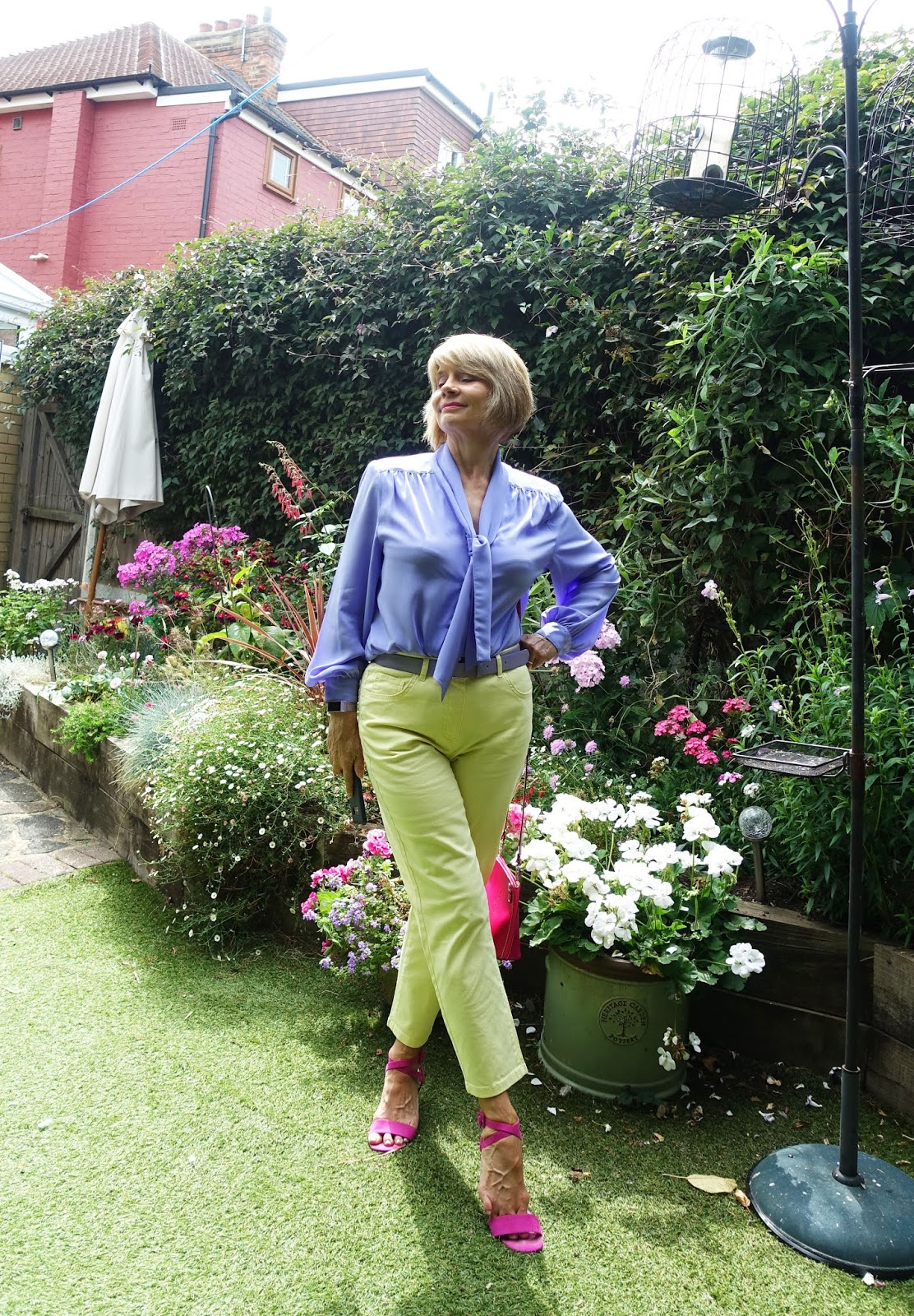 Over 50s blogger Gail Hanlon in lilac and yellow in a summer garden