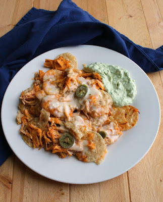 plate of buffalo chicken nachos with avocado sour cream