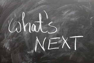"A blackboard with the words ""what's next"" written on it in chalk"