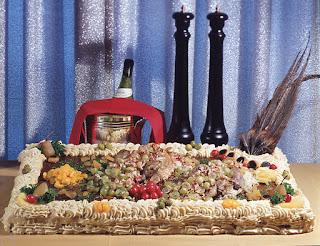 Kuvassa suorakaiteen muotoinen voileipäkakku, jonka päällä runsaasti täytteitä, ja reunoilla smetanaa. Takana kuohuviinipullo ja kaksi maustemyllyä.